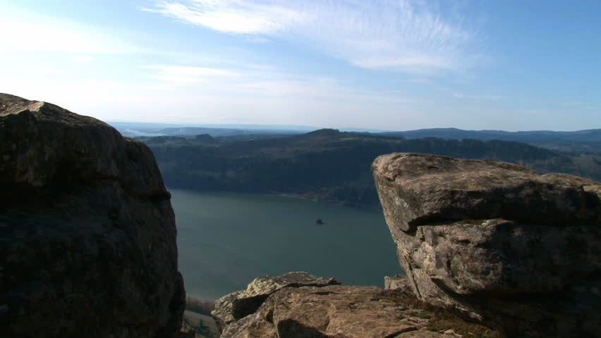 Person hiking and leaping across rocks atop cliff in Oregon up the Gorge. | Shutterstock HD Video #2359127