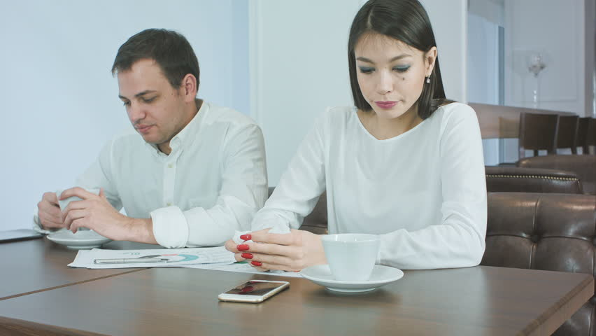 Two coworkers not feeling well and drinking hot tea during lunch in a cafe | Shutterstock HD Video #23597047