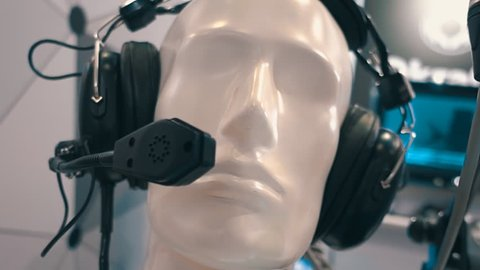 Black professional headphones with a microphone on a head of white mannequin in a store professional audio equipment. Shot in motion