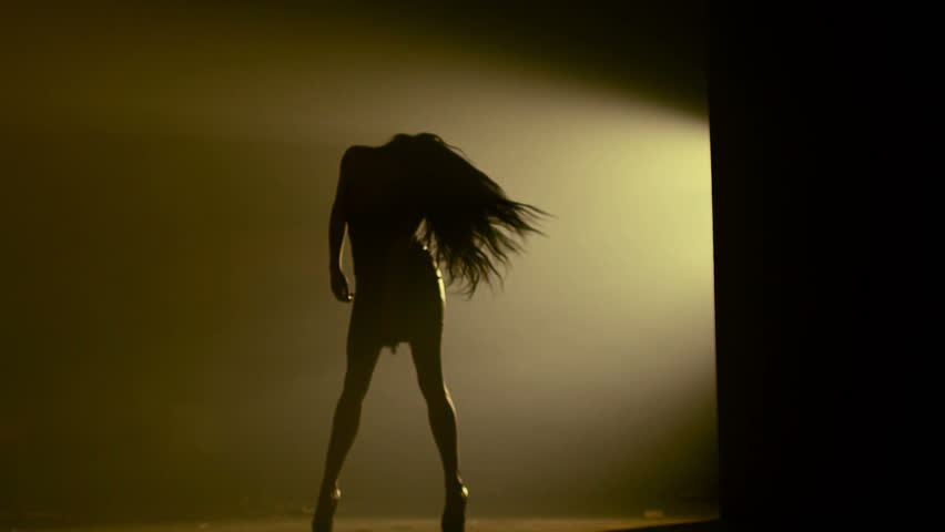 Beautiful dancer demonstrating her perfect sensual figure and dancing on dark brown background with strobe light effect . Shot on RED HELIUM Cinema Camera in slow motion.