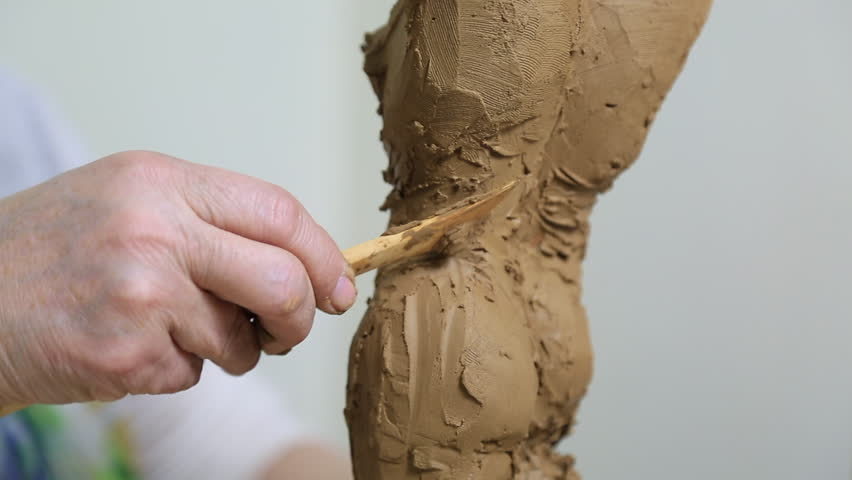 Sculptor Uses Tool To Sculpt Side Of Statue