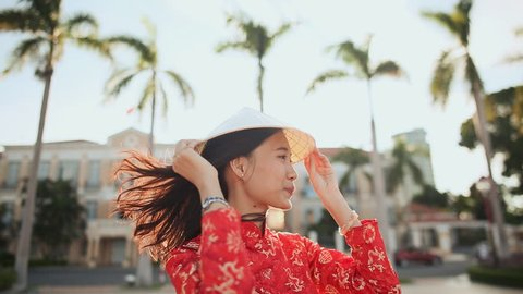 Vietnamese girl puts on a national cap Non La in the rays of the evening sunset in the city of Da Nang