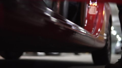 Man getting into car on drivers side. Closeup view from below, legs in boots.