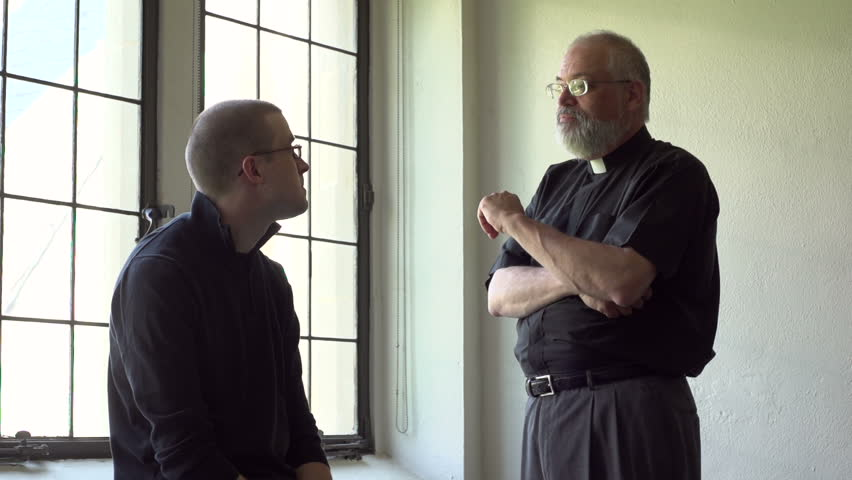 Priest talking with parishioner in a church