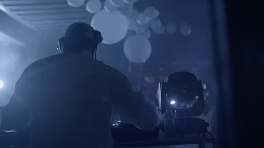 Slow motion shot of a DJ Mixing Tracks in Night Club. Back of DJ raising his hands and crowd dancing at during party. | Shutterstock HD Video #23681647