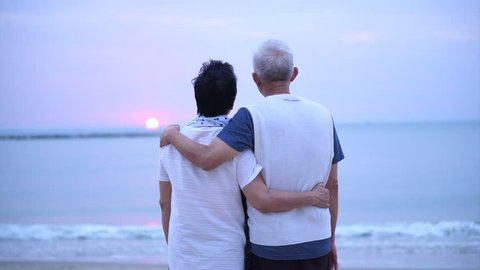 Loving Asian senior couple happy together at ocean sunrise