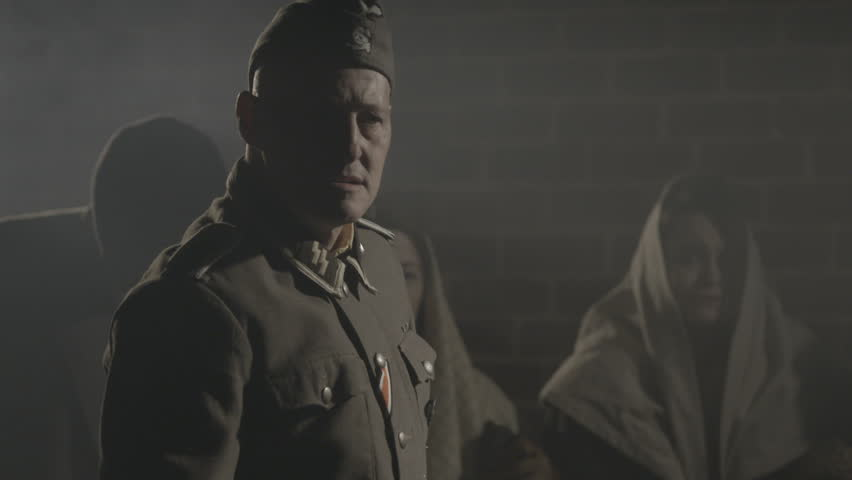 EUROPE - APRIL 2015 - Moody and edgy epic WW2 Re-enactment, recreation -- Nazi SS Soldiers round up Civilian prisoners in Europe in 1930s, 1940s and search then march onto trains with steam and night