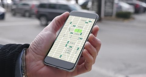 A man uses his smartphone to observe ride sharing traffic patterns on an interactive map in a city.