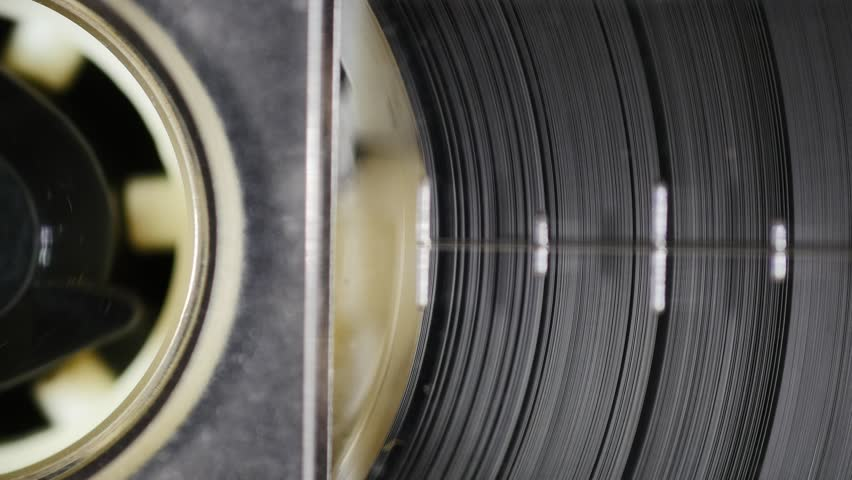 Spinning magnetic tape in tape drive. Seamless loop. 4K, static macro shot. Close up of audio cassette tape in use sound recording in a cassette player