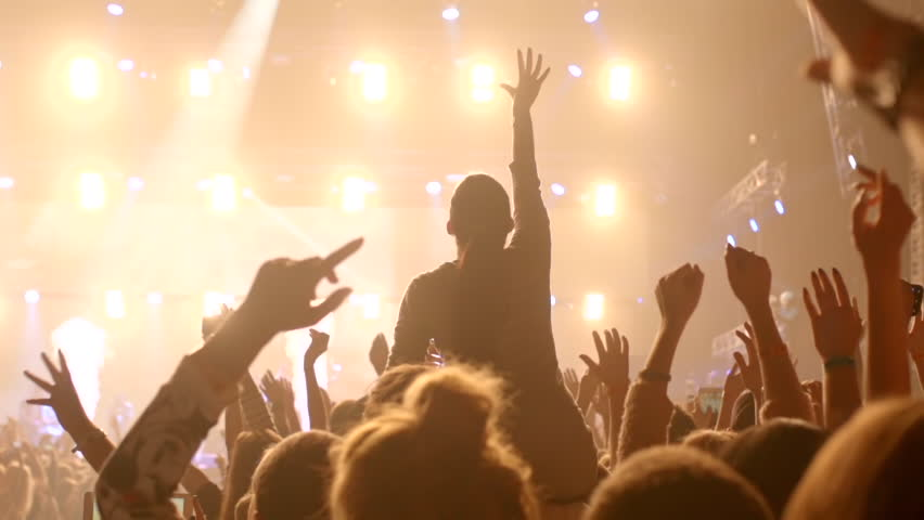 Girl at a concert seating on shoulders & raising her hands.