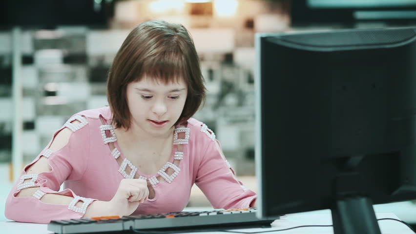 Girl with Down syndrome sitting at a computer at home and typing text.