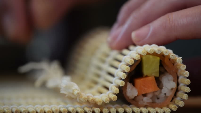 Close-up of professional chef's hands rolling a sushi roll on seaweed mat