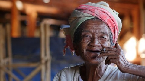 Happy old lady of Pa'O ethnic minority smoking a Burmese cigar and smiling at Indein village near Inle Lake, Shan State, Myanmar.