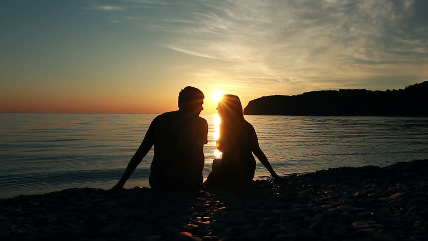 Couple on the shore of the sea, Romantic Couple at Sunset. Two people in love at sunset. Man and woman on the beach | Shutterstock HD Video #2379587