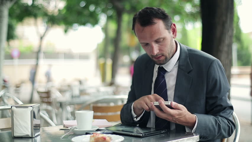 Businessman working with tablet and smartphone in cafe