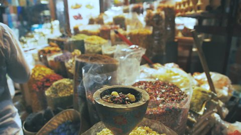 Eastern Market with spices in Emirates. Close-up of spices in different colors on the market in the UAE. Hibiscus, curry, turmeric. Shop owner at spice market arranges display