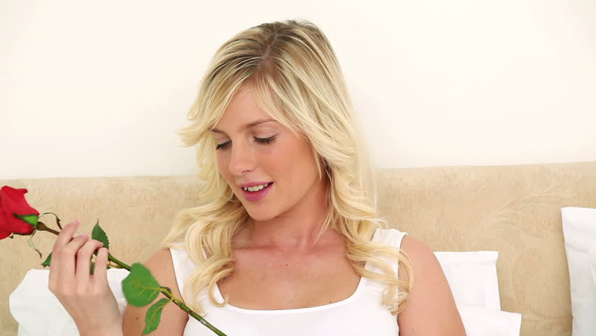 Young blonde smelling a rose on her bed