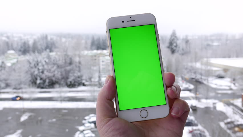 Coquitlam, BC, Canada - February 05, 2017: Man holds a blank smartphone and tapping on green screen with snow nature background.