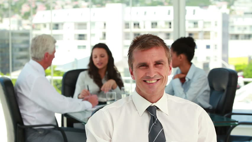 Portrait of a businessman with colleagues in meeting in background in a bright office | Shutterstock HD Video #2383637
