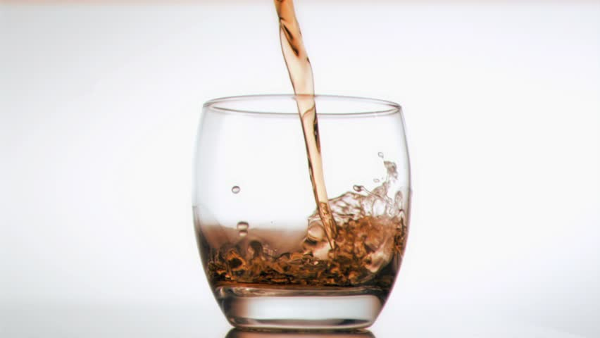 Ice and whiskey been poured in super slow motion against a white background