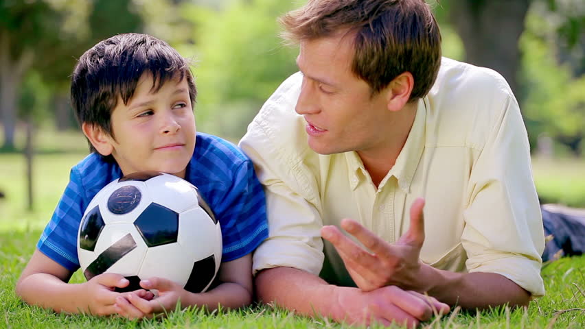 Happy father and son lying on the grass with a soccer ball in the countryside