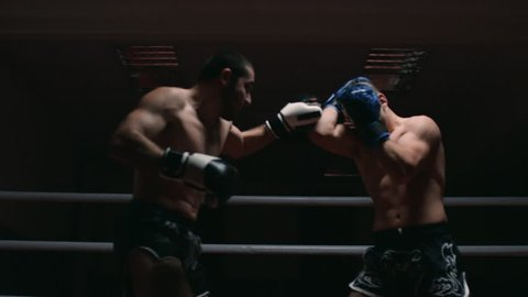 Two muscular mixed martial arts athletes fighting in the ring in slow motion