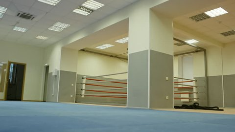 Low angle tracking shot of empty gym with boxing ring for training
