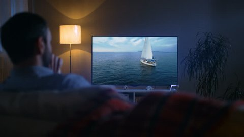 Back View of a Man Sitting on a Couch Watching Romantic Movie with Yachting and Camping in it on His Big Screen TV. It's Evening.