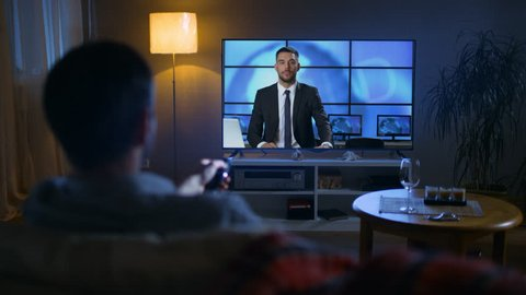 Back View of a Man Sitting on a Couch Watching Breaking News on His Big Screen TV. It's Evening. Shot on RED EPIC-W 8K Helium Cinema Camera.