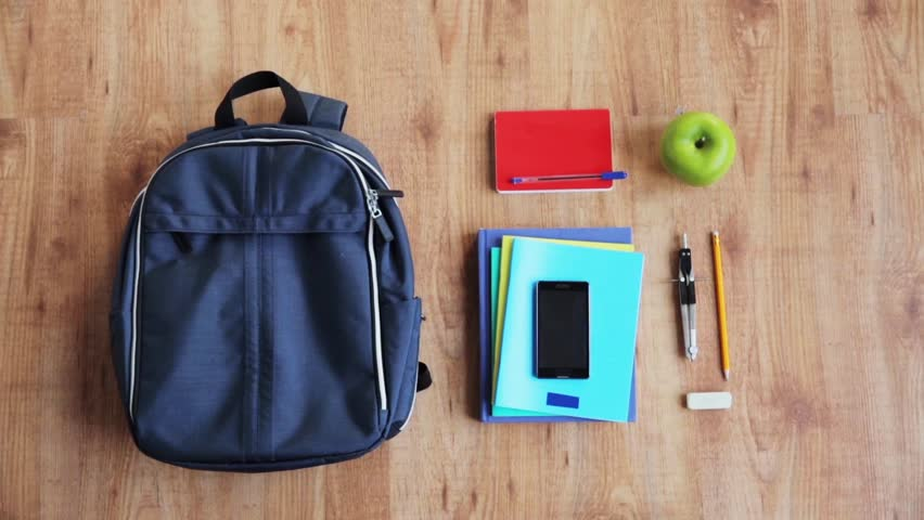 people, school supplies, education and personal stuff concept - hands packing schoolbag