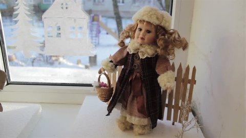 Doll on the window in winter coats and wearing hat