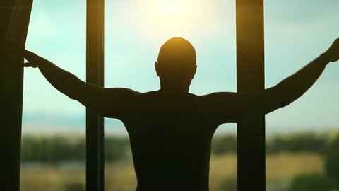 Man opens the curtains in the morning and reaches for the light. Young man opens big window curtains and lets the sun light in the room