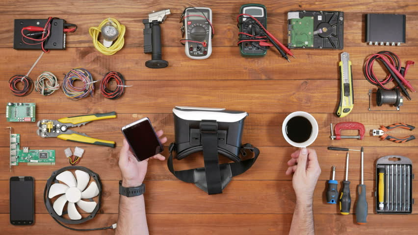 Male engineer repairman uses virtual reality headset. Wooden table top view. Inserts the phone and puts on his head | Shutterstock HD Video #23904130
