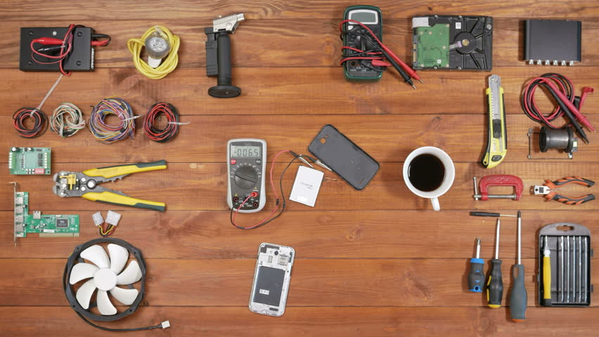 Man repairing a mobile phone. Checks parts inside the device. Wooden table top view. | Shutterstock HD Video #23904187