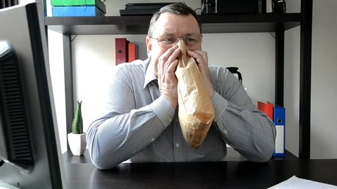 Middle aged man sitting at the desk breathes into a brown paper bag as a remedy for panic attack