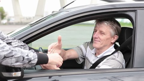 Mature Caucasian man get ignition key sitting in new car, starting and get a move on