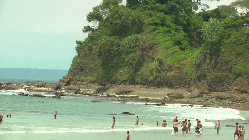 Beach and ocean with people bathing near a rocky cliff with natural surroundings (medium shot). Toma amplia de la playa con turistas y peñazco con vegetación natural al fondo.