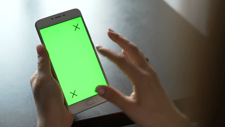 One person use cellular telephone with touch green screen for browsing social networks and communicating closeup. Girl, holding in hand portable gadget close up, as image of tech accessibility concept #23974837