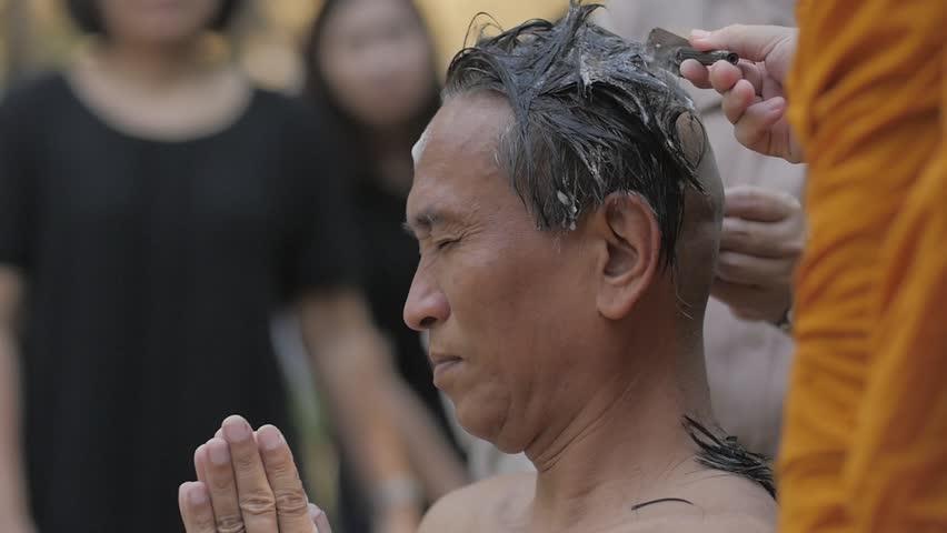 BANGKOK, THAILAND - NOVEMBER 15 : Thai people ordain Buddhist .monks hair shave young men to be ordained a new monk.on BANGKOK, THAILAND - NOVEMBER 15 2016 .Slow motion,high speed camera #24013807