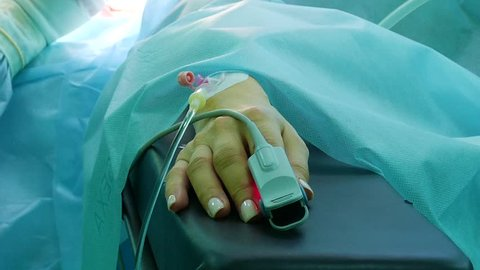cardiograph on the patient's finger during surgery