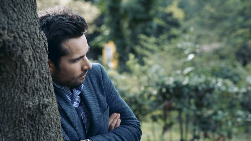 Close up on pensive handsome man leaning to a tree in a park #24024517