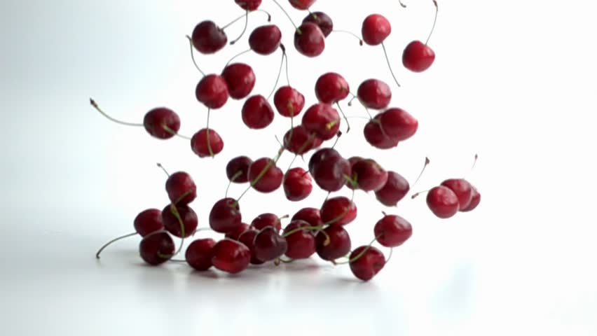 cherries falling on white background in slow motion