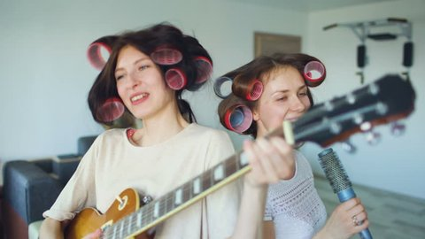 Two funny girls singing with comb and playing electric guitar, dancing, singing,  and having fun at home.
