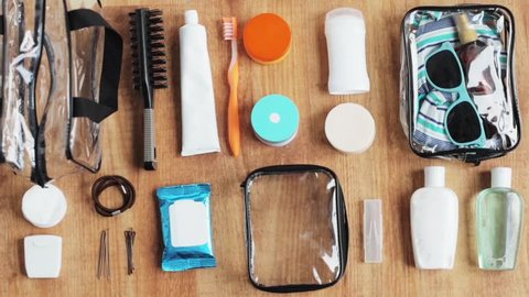 people, toiletry and storage concept - hands packing cosmetics and personal stuff to bag for travel
