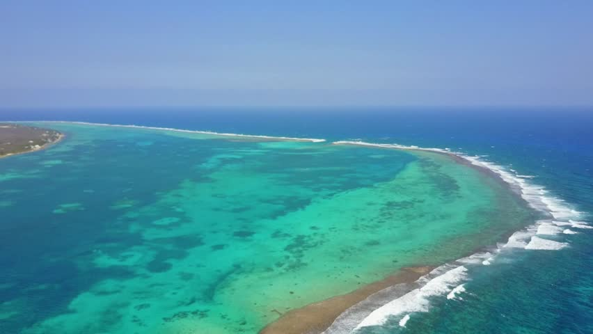 Aerial view of a caribbean barrier reef with blue and green depth changes of the crystal clear water.