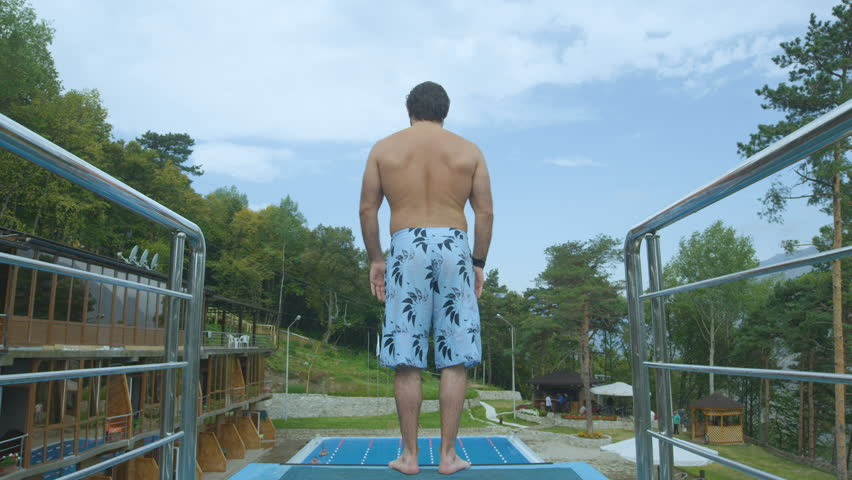 backside slow motion young man stands on swimming pool tower edge ready to jump and camera follows jumping