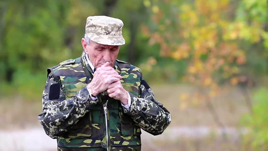 Hunter smokes a cigarette in the forest. Senior man in uniform stands on a post in the wood. Retired officer smokes a cigarette.. Elderly person in military uniform smokes a cigarette