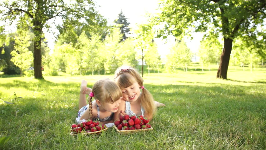 Laughing children lie on the grass. They eat strawberries
