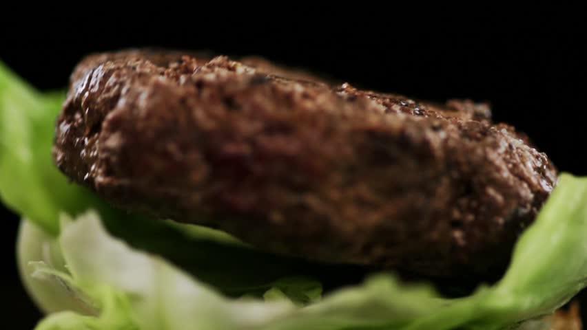 SLOW MOTION FOOD: big juicy steak falls on burger