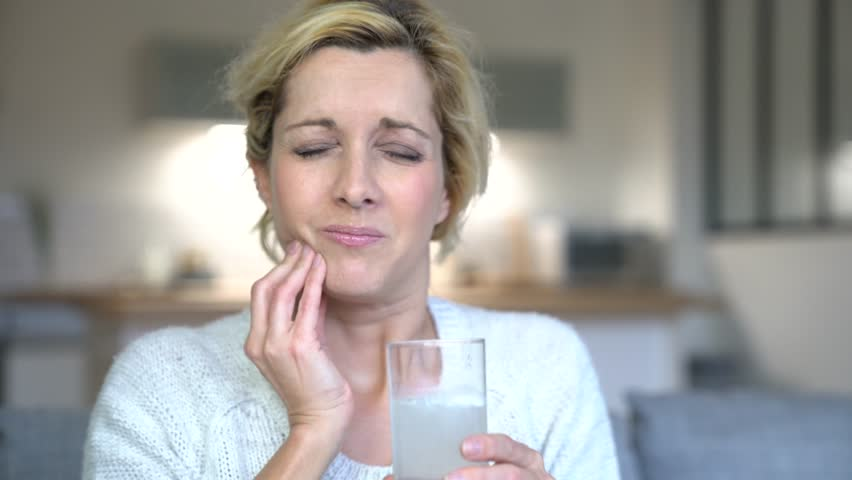 Middle-aged woman taking tylenol to ease toothache